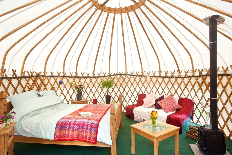 inside of white yurt with wooden frame shows a large bed, a small table with flowers on it and a woodburning stove with flue pipe going out of ceiling. Also a sofa bed with red and purple cushions
